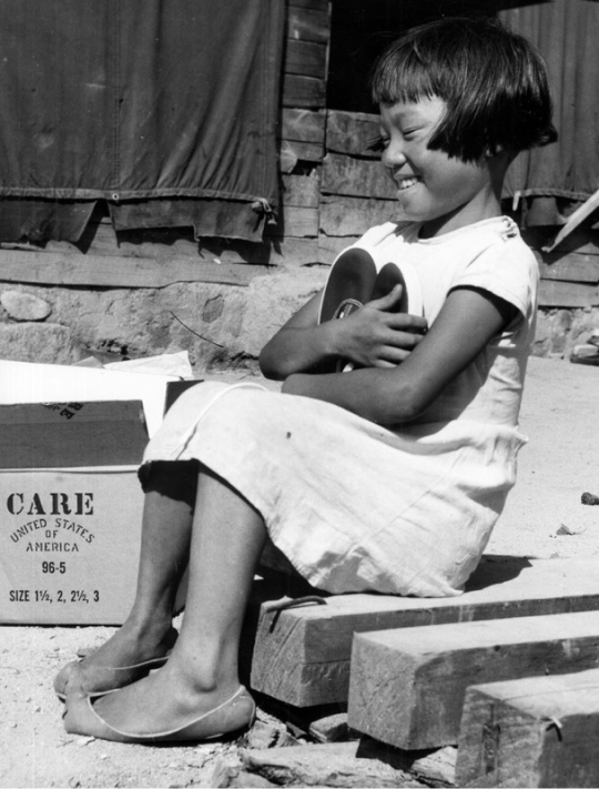 A young Korean girl sits on a curb and smiles while hugging a pair of shoes.