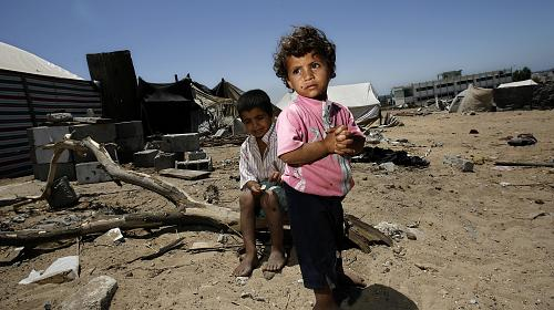 Children stand outside the remains of their family home that was destory during the recent conflict on Thrusday, 17 July, 2009, in the Gaza Strip. (Warrick Page/Getty Images for Care International)