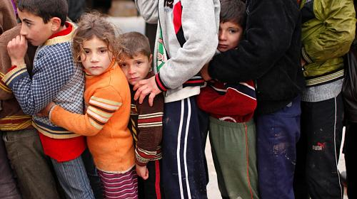 Syrian refugee children queue as they wait to receive aid from Turkish humanitarian agencies.