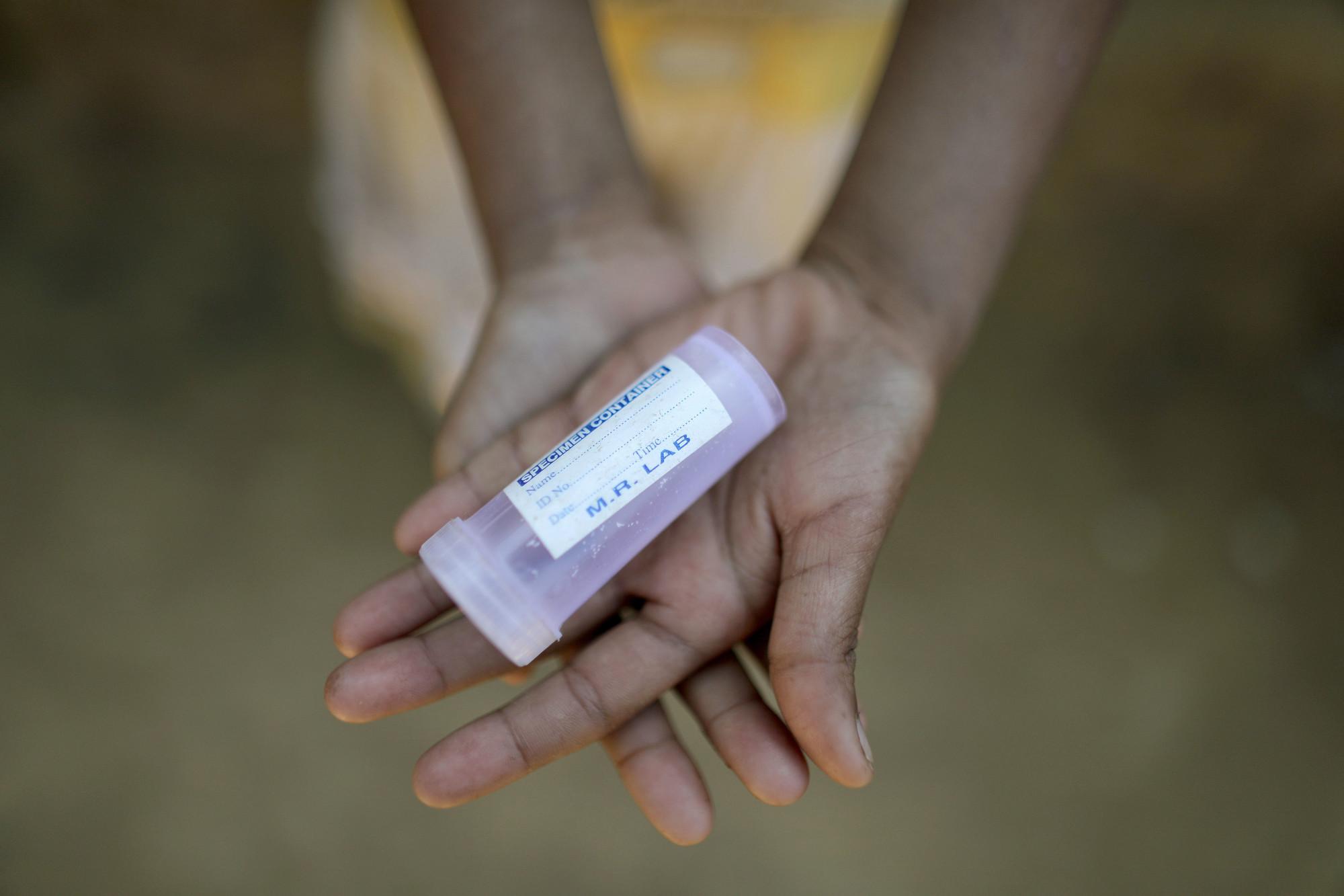 Rokhaida, de 8 años, lleva un contenedor médico vacío. En el campamento de Bangladesh, muchos de los refugiados rohingya están enfermos y necesitan desesperadamente servicios médicos.