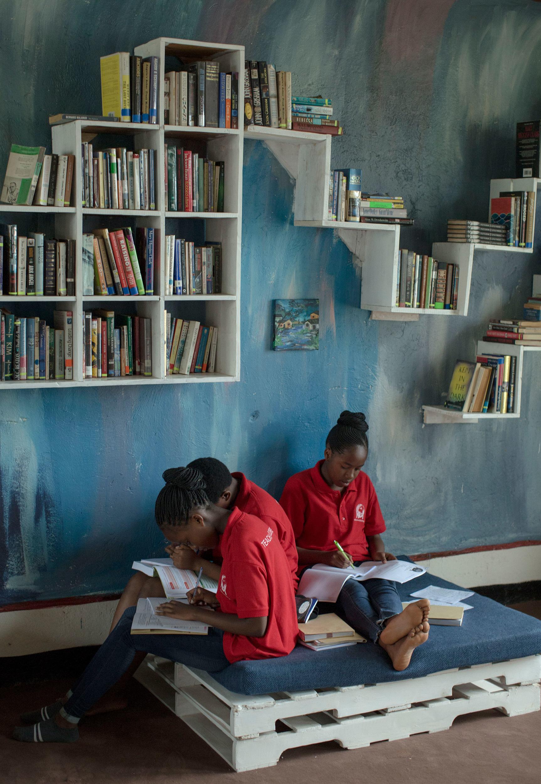 Estudiantes de White Dove Global Prep leyendo en la biblioteca de su escuela. Imagínese que ayudamos a diseñar y abastecer la biblioteca con libros.