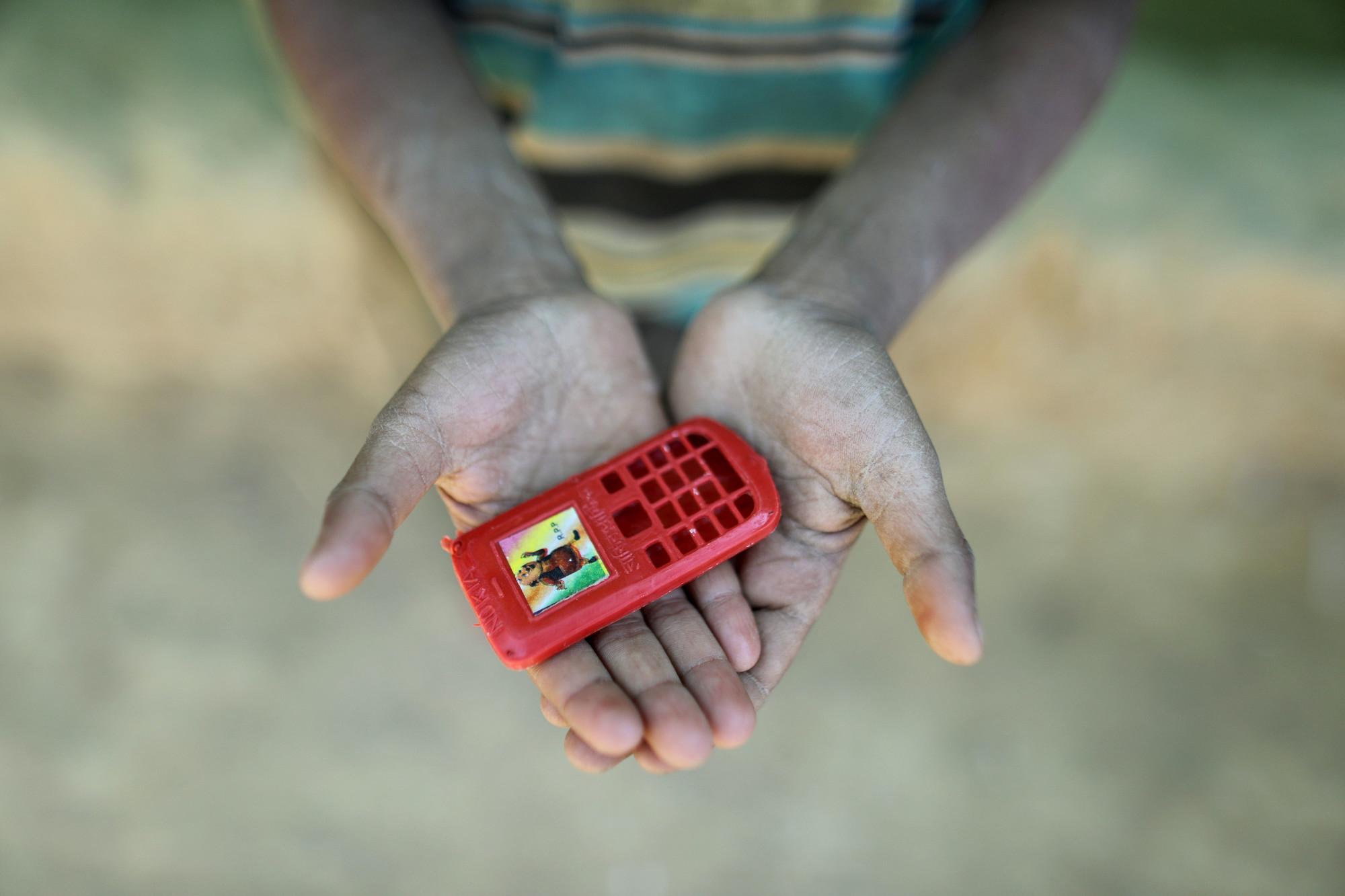 Mohammad encontró este teléfono de plástico en una caja de bocadillos que recibió. El niño de 10 años huyó de Myanmar después de que su casa fuera incendiada. Un día quiere tener un teléfono real para llamar a sus amigos.