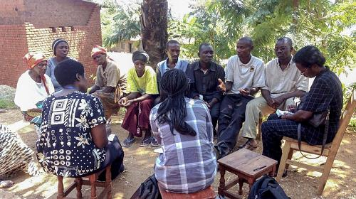 A community group of women and men, members of a Village Savings and Loan Association, meet in a village in Burundi, where VSLAs economically empower members to take control of their finances and futures.