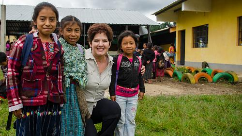 CARE supporter Lynn Jeffords poses with students at the Escuela Oficial Rural Mixta Los Planes, a school participating in CARE's Qach'umilal (Guiding Star) Girls project. The project promotes reducing gender inequality gaps supporting educational models for indigenous children and adolescents living in Santa Lucia Utatlán, Guatemala.