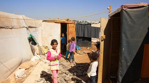 Children play outside of their homes – comprised of tents, plywood and tarps – at a refugee encampment in Zaatari, Jordan.