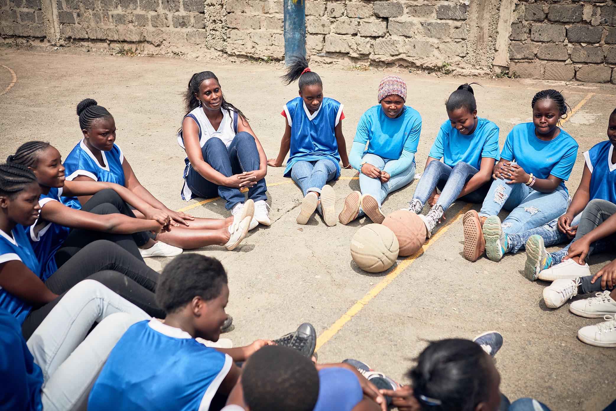 Peninah reúne a uno de los equipos de baloncesto Safe Spaces para una discusión después de la práctica. Foto: Juozas Cernius / CARE