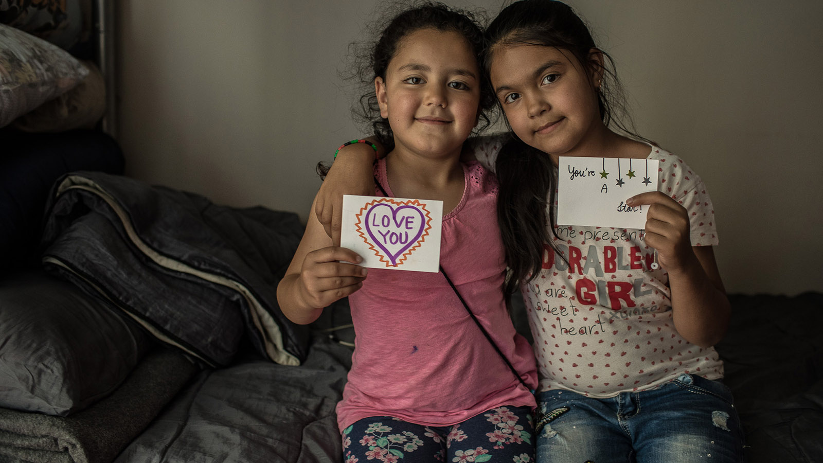 Two girls share the letters they received as part of a letter exchange between American students and international refugees.