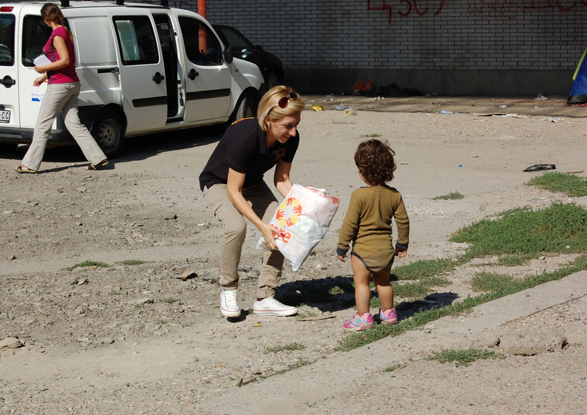 A woman wearing a navy top bends down to offer a bag to a small child. The bag has the CARE logo on it.