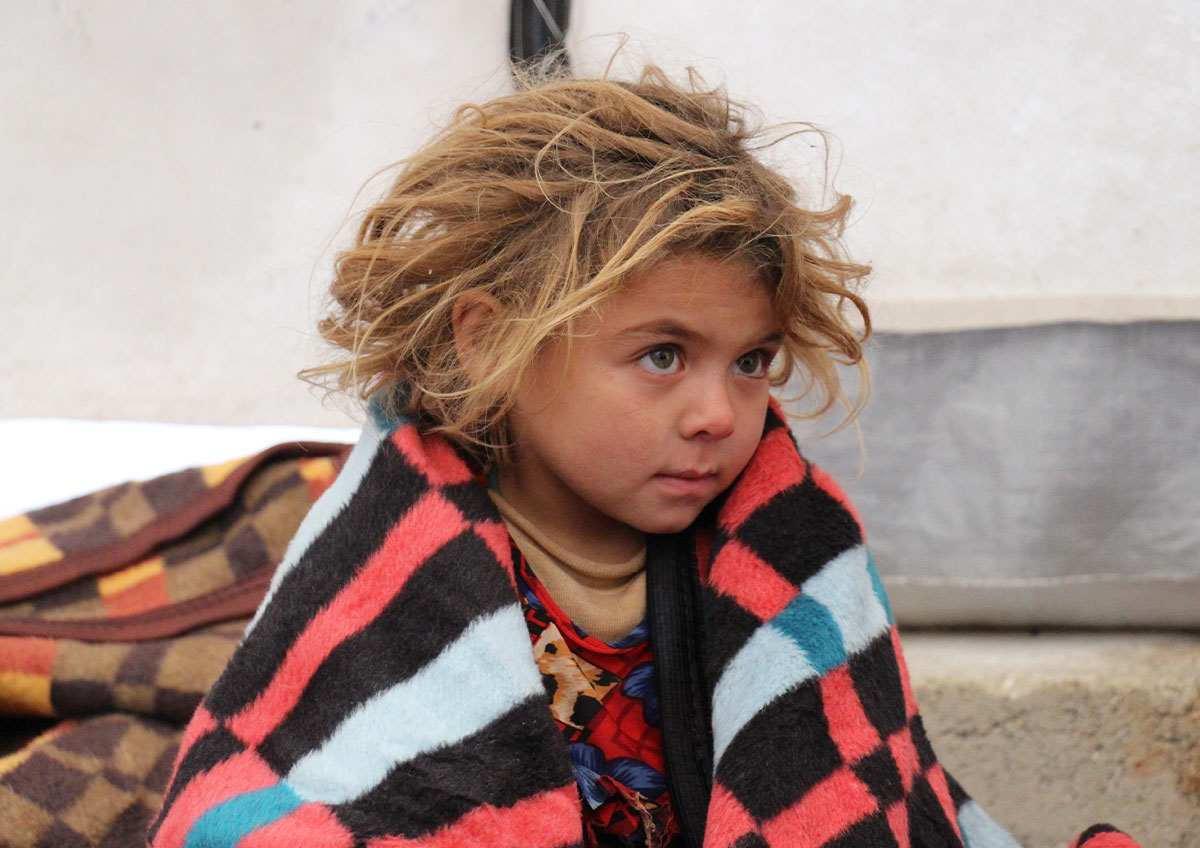 A young child sits in a tent with a striped blanket wrapped around them.