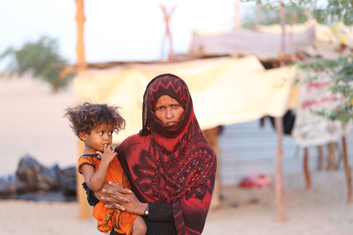 A woman wearing a red patterned hijab holds her young child on her hip. Her child is wearing a bright orange garment. Behind them is a white makeshift tent.