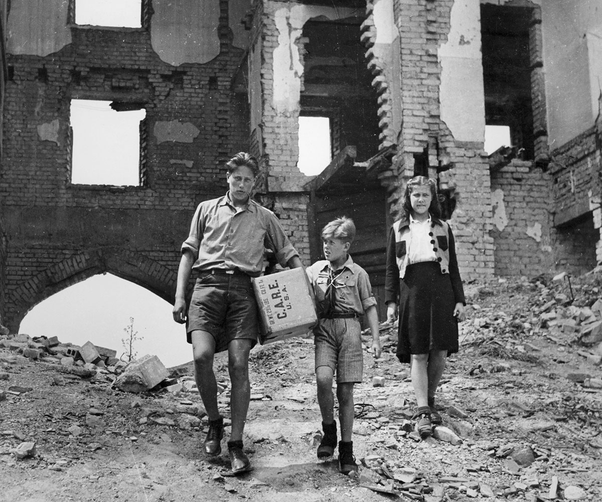 A man holding a CARE Package walks through the rubble of Berlin with his son and daughter.