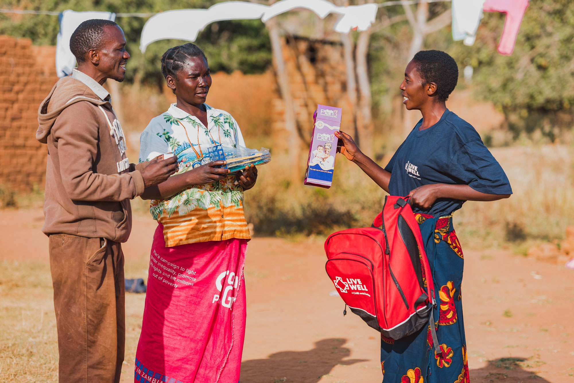 A woman wearing a dark blue Live Well shirt shows supplies to a man and woman.