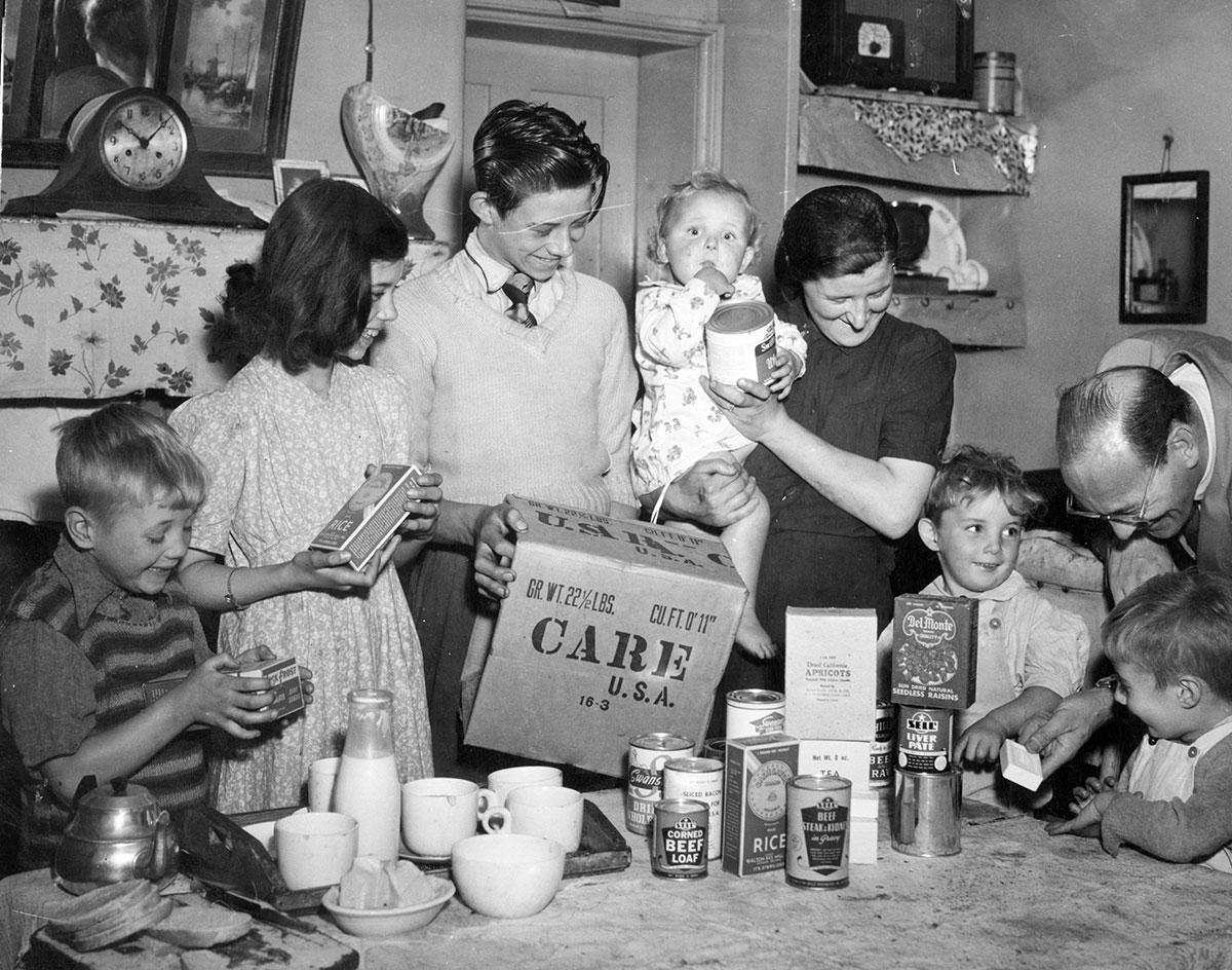 A large family convenes around a table filled with food items from a CARE Package.