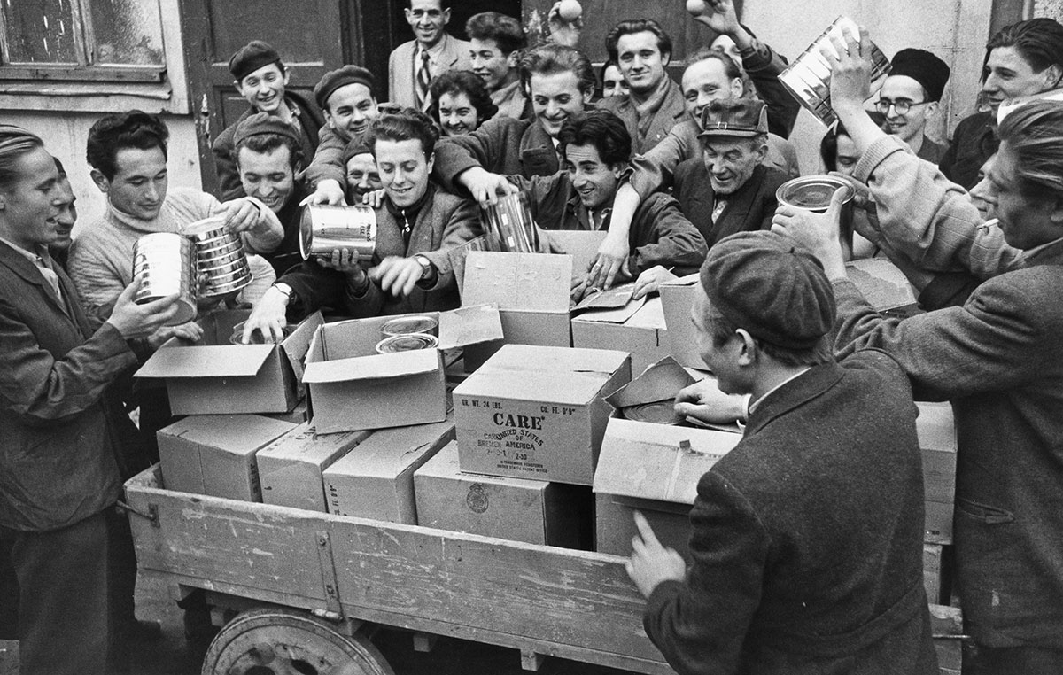 A large group of men crowd around a truck delivering new CARE Packages.