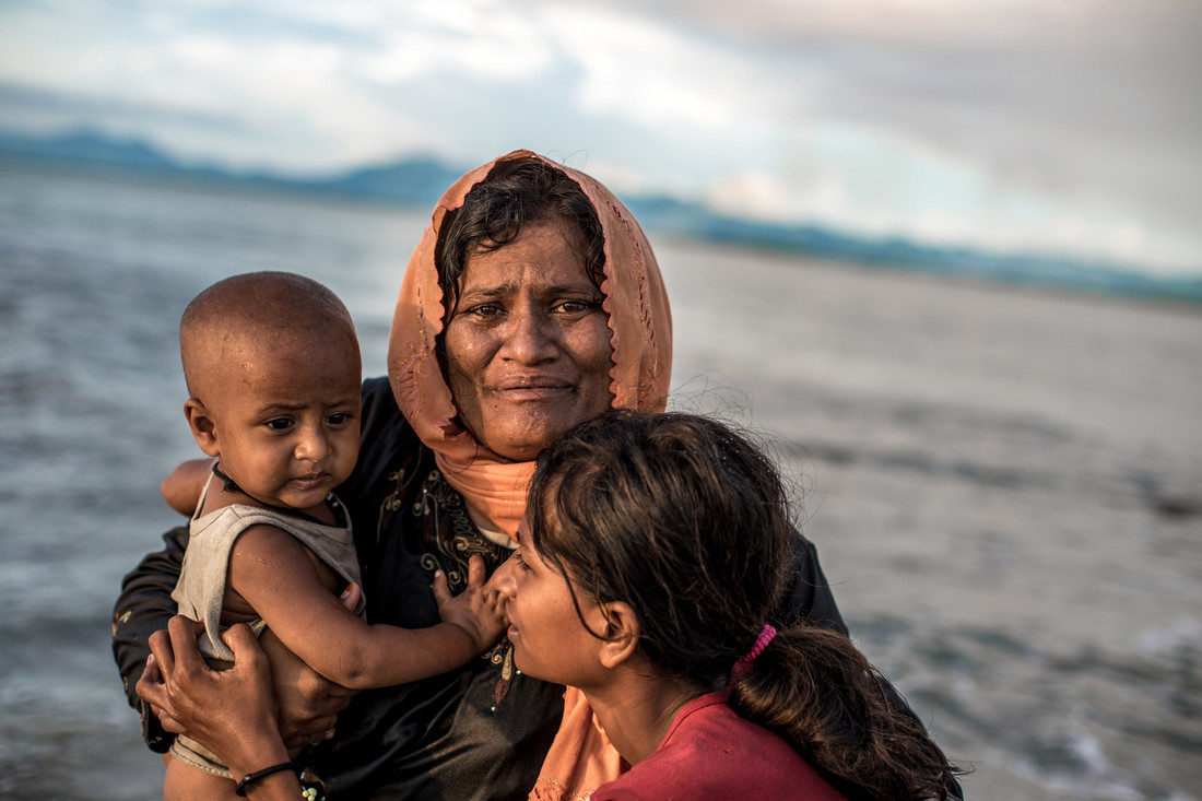 A distressed woman huddles with two children, one of whom is a baby, in front of the ocean.