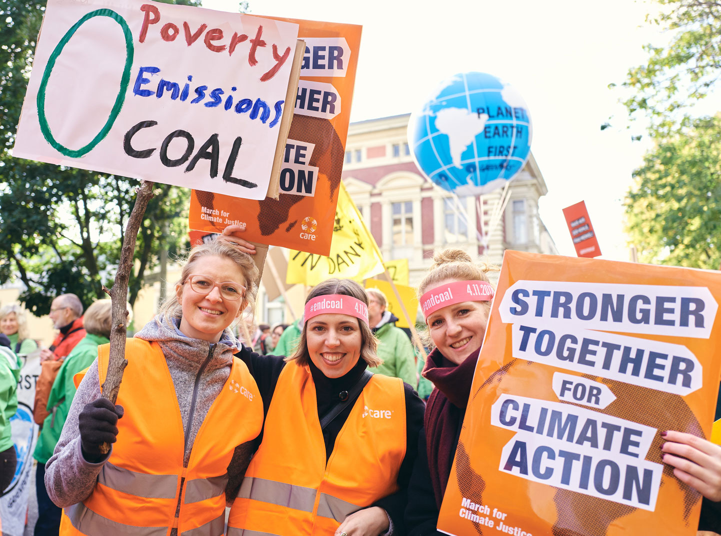 Three women wearing orange vests smile at a CARE for Climate Action march. One is holding a sign that says,