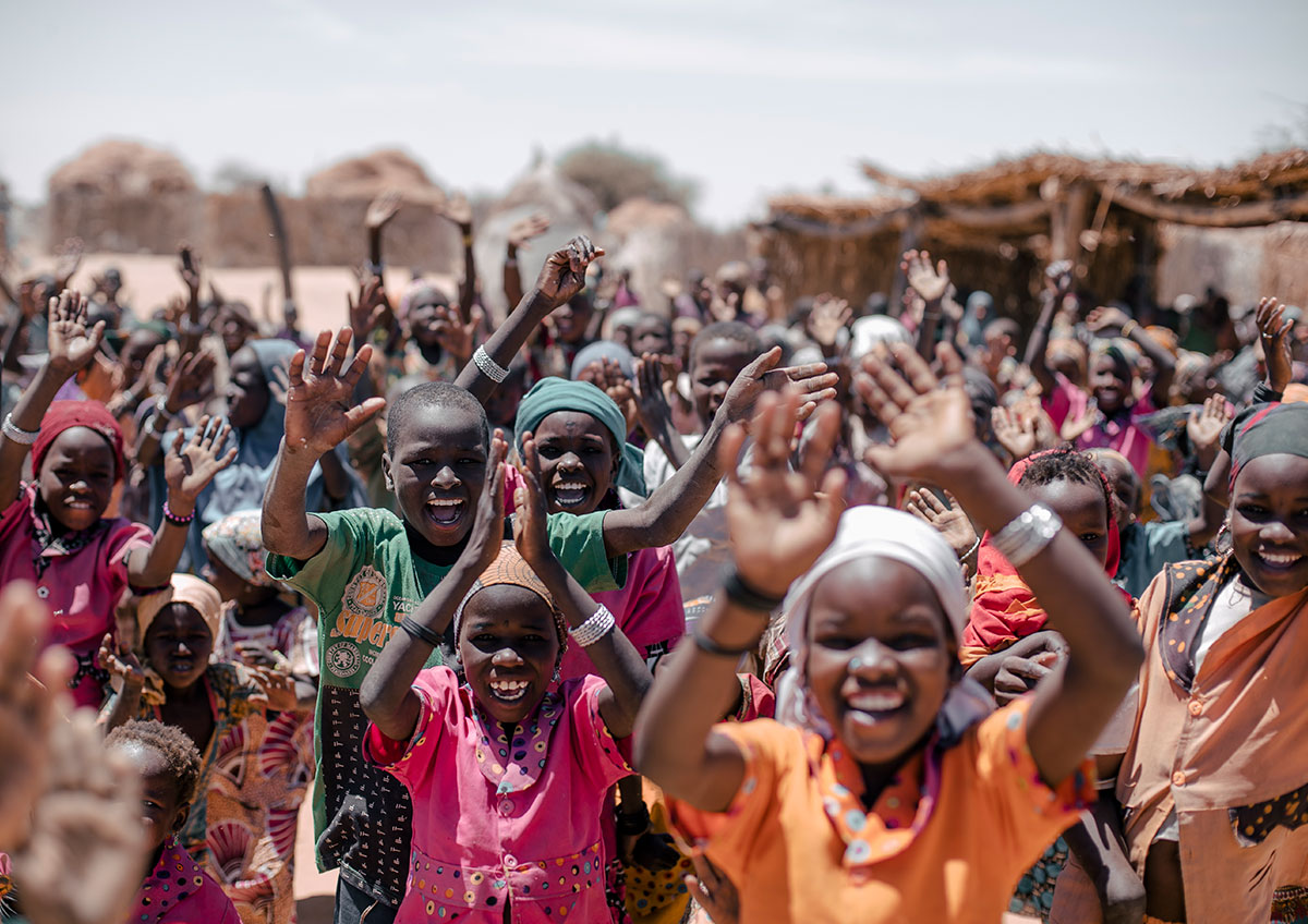Un grupo de niños anima y levanta la mano en celebración.