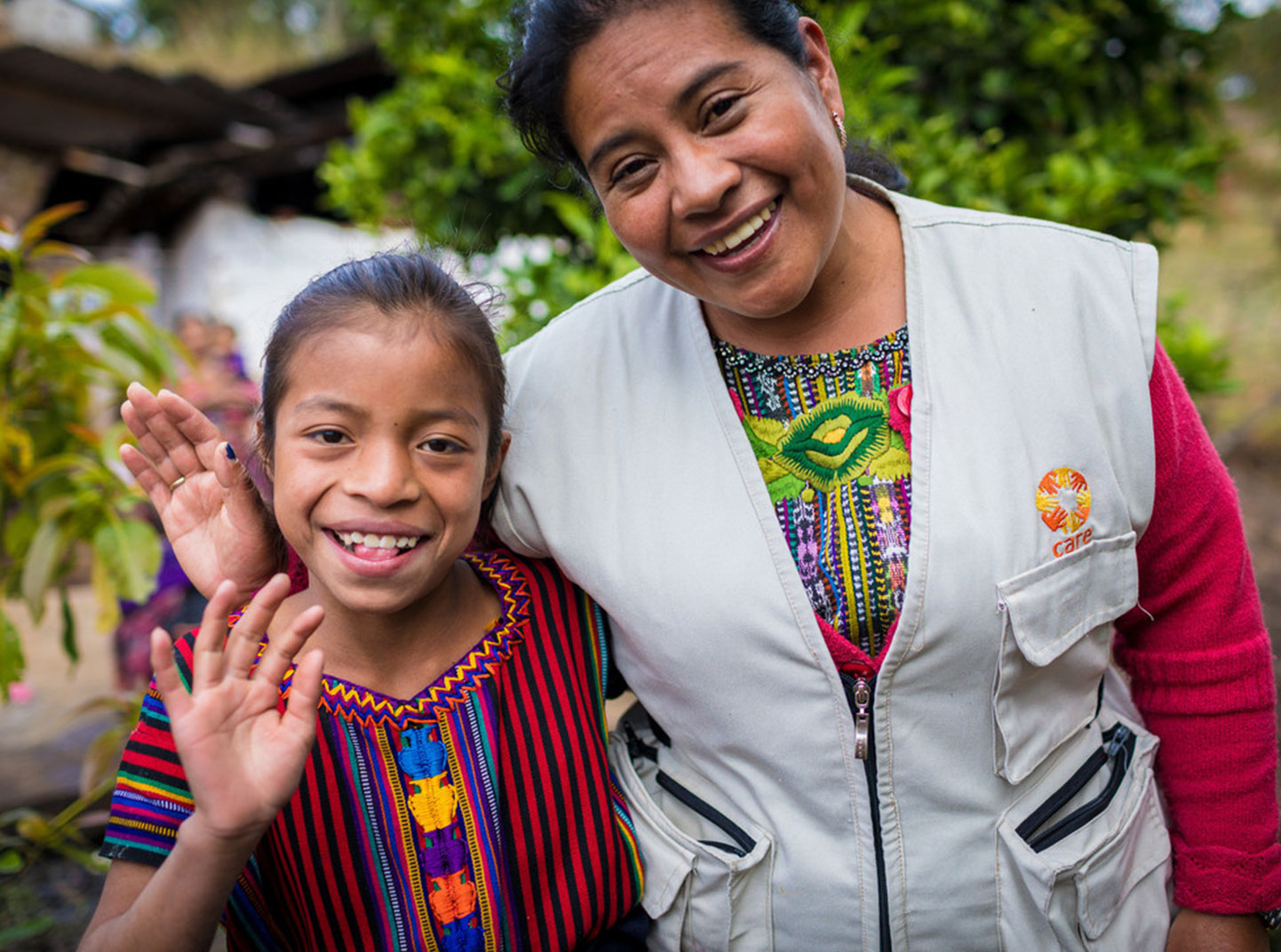 A care staffer wearing a vest stands next to a young girl wearing a brightly patterned shirt. They both smile and wave at the camera.