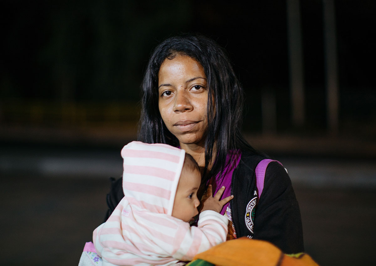 A woman with long hair holds her baby to her chest. Her baby is wearing a light pink and white striped hooded onesie.