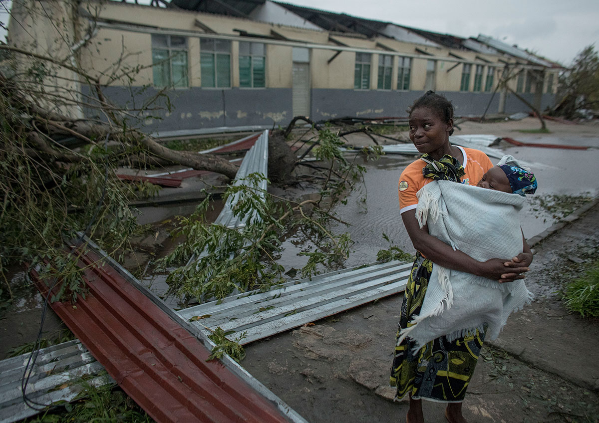 A woman holds her young child in a blanket while walking through a street filled with fallen tree branches and debris.