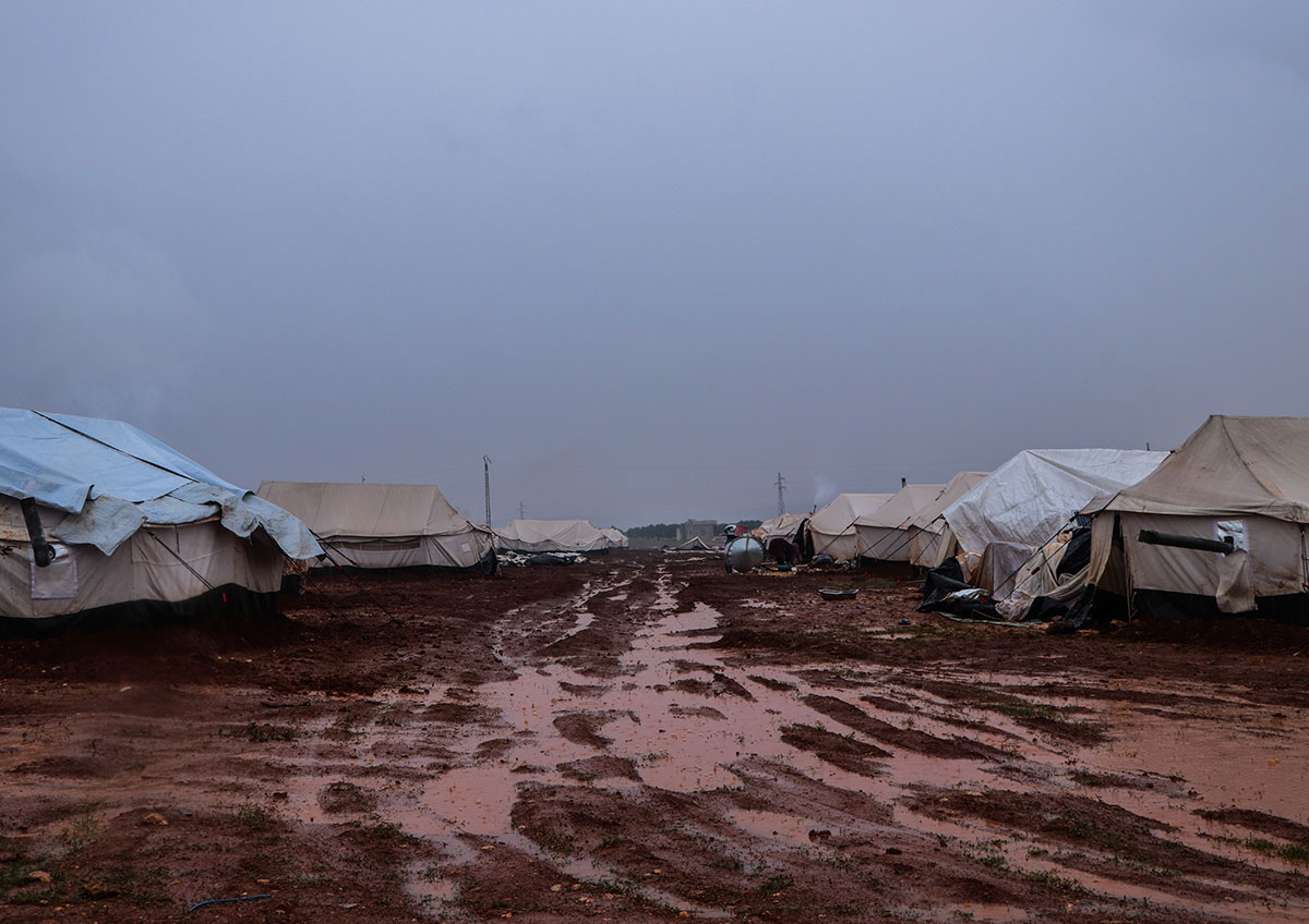 Large canvas tents sit in place on either side of a muddy road.