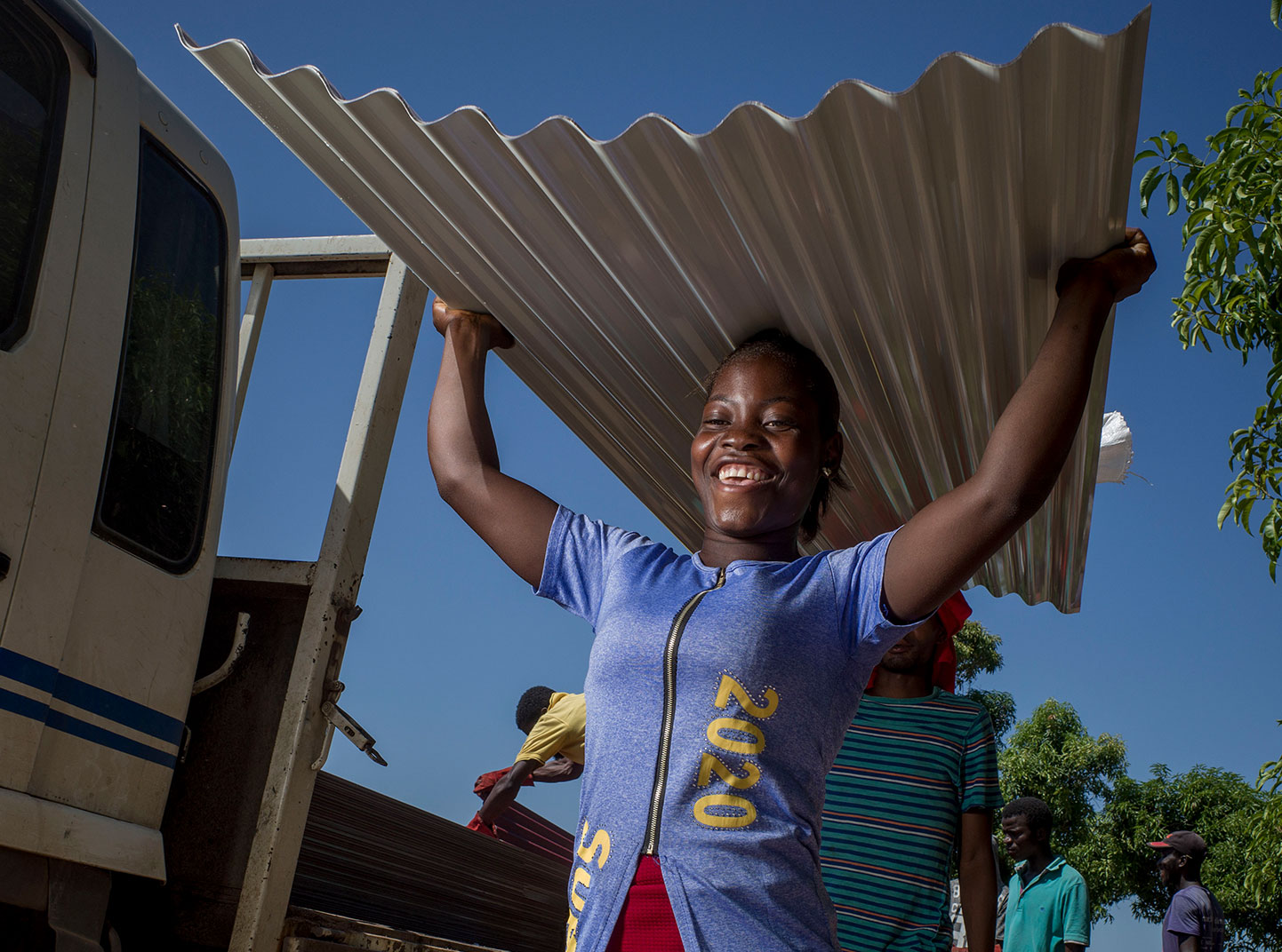 Uma mulher sorri enquanto carrega uma grande peça de metal.