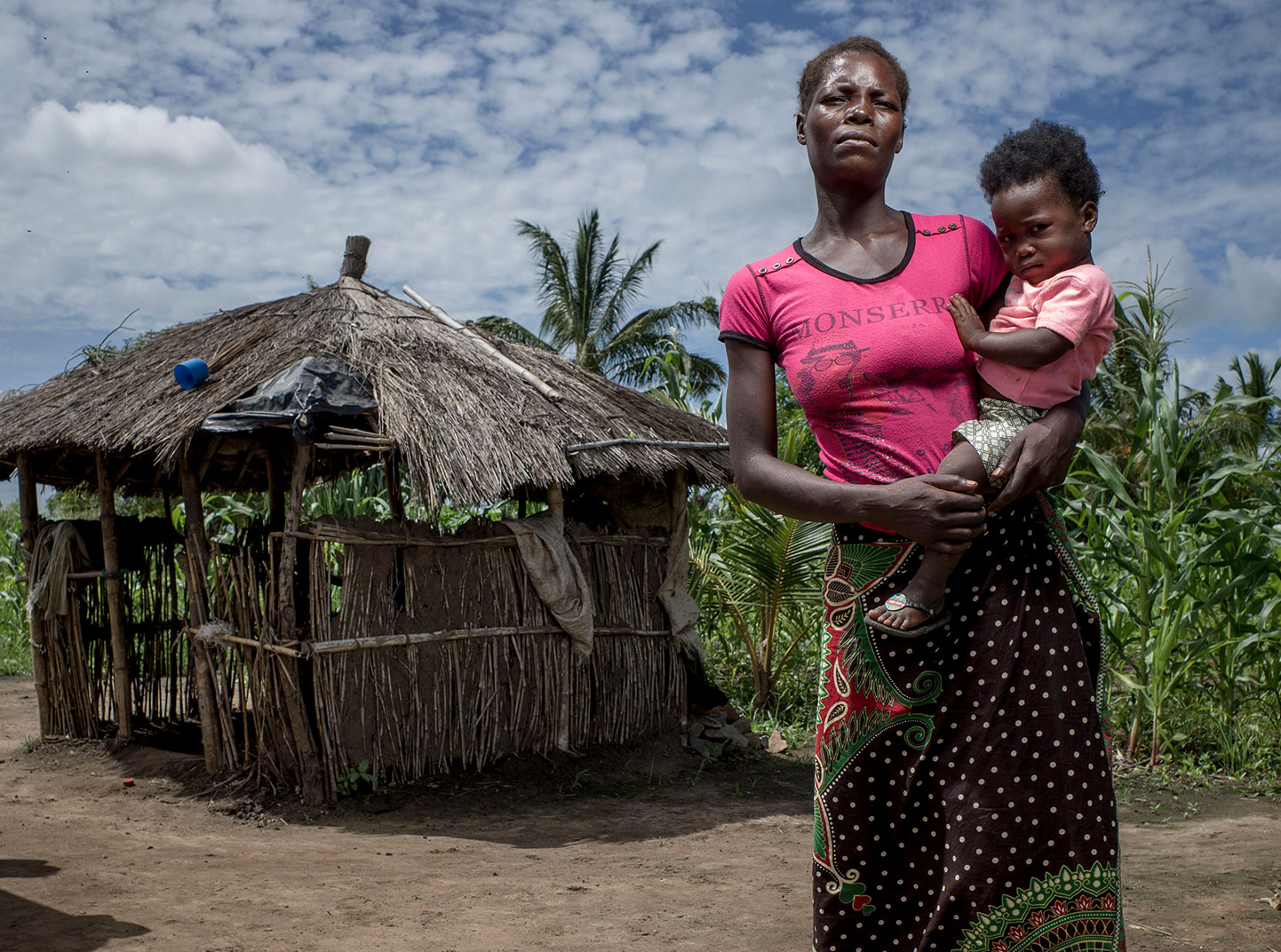 A woman holds her small child in front of a hut.