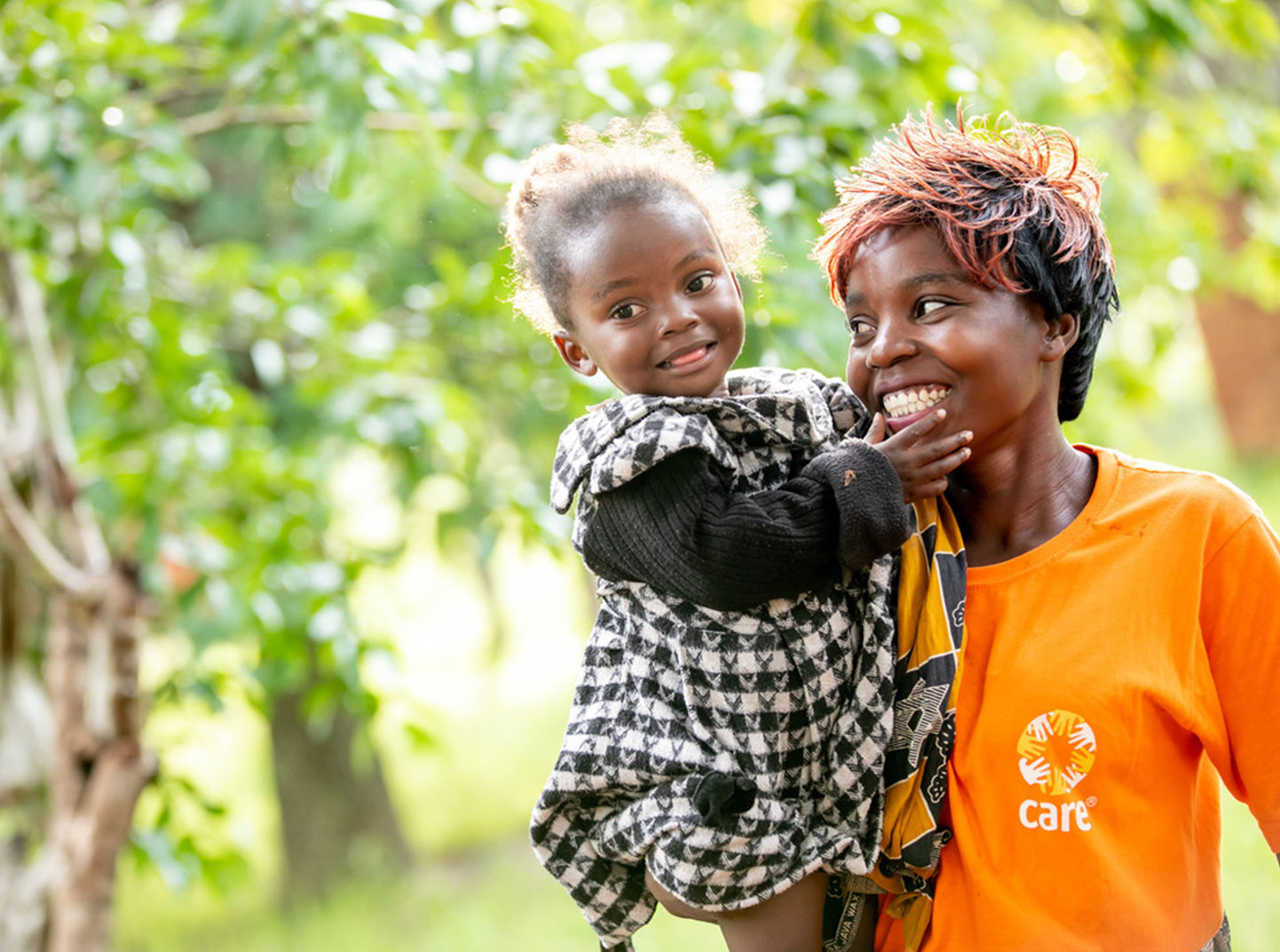 Un membre du personnel de CARE portant une chemise orange vif de CARE sourit tout en tenant une jeune fille vêtue d'une robe à carreaux noir et blanc.