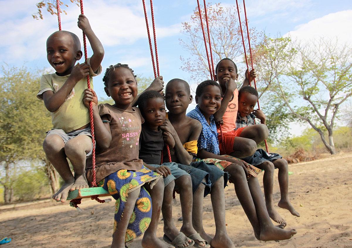 Um grupo de crianças sorri e ri sentado em um grande balanço verde.