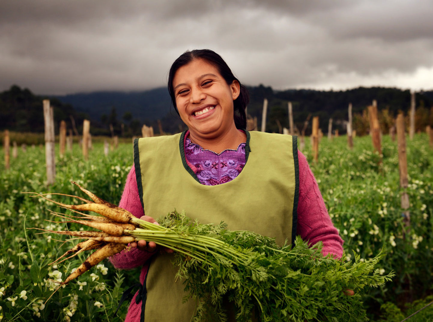 A woman stands in the middle of a large field and beams while showing off some carrots she's just pulled from her crop garden.