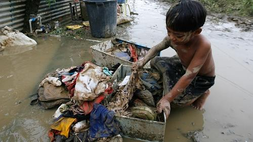 A survivor of Typhoon Ketsana sorts his family's soiled clothes in the Silangan village in suburban Quezon city, north of Manila on September 28, 2009. (Reuters/Erik de Castro, courtesy