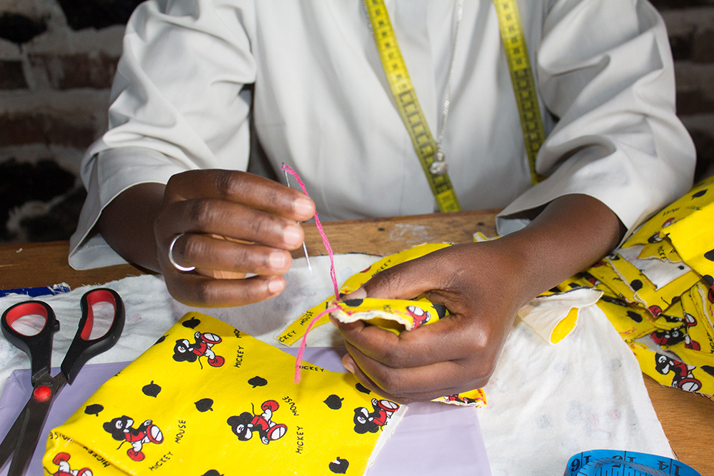 After participating in a CARE initiative designed to improve the sexual and reproductive health knowledge of youth and adolescents, Sister Philotte began manufacturing pads to increase access for adolescent girls. Photo: Ninon Ndayikengurukiye/CARE