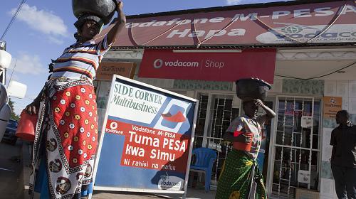 Este estande da M-Pesa / Vodacom está localizado em Arusha, na Tanzânia, e oferece às pessoas acesso para gerenciar seu dinheiro com o uso de tecnologia. Mpesa é um banco móvel através do uso do telefone celular. Os clientes que usam Mpesa podem receber e enviar dinheiro e pagar contas usando seu dispositivo móvel.