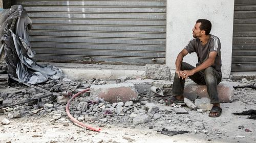 A man sits outside the home of the Al Yasje family which was destroyed in an Israeli airstrike in the Jabalaya district of Gaza.