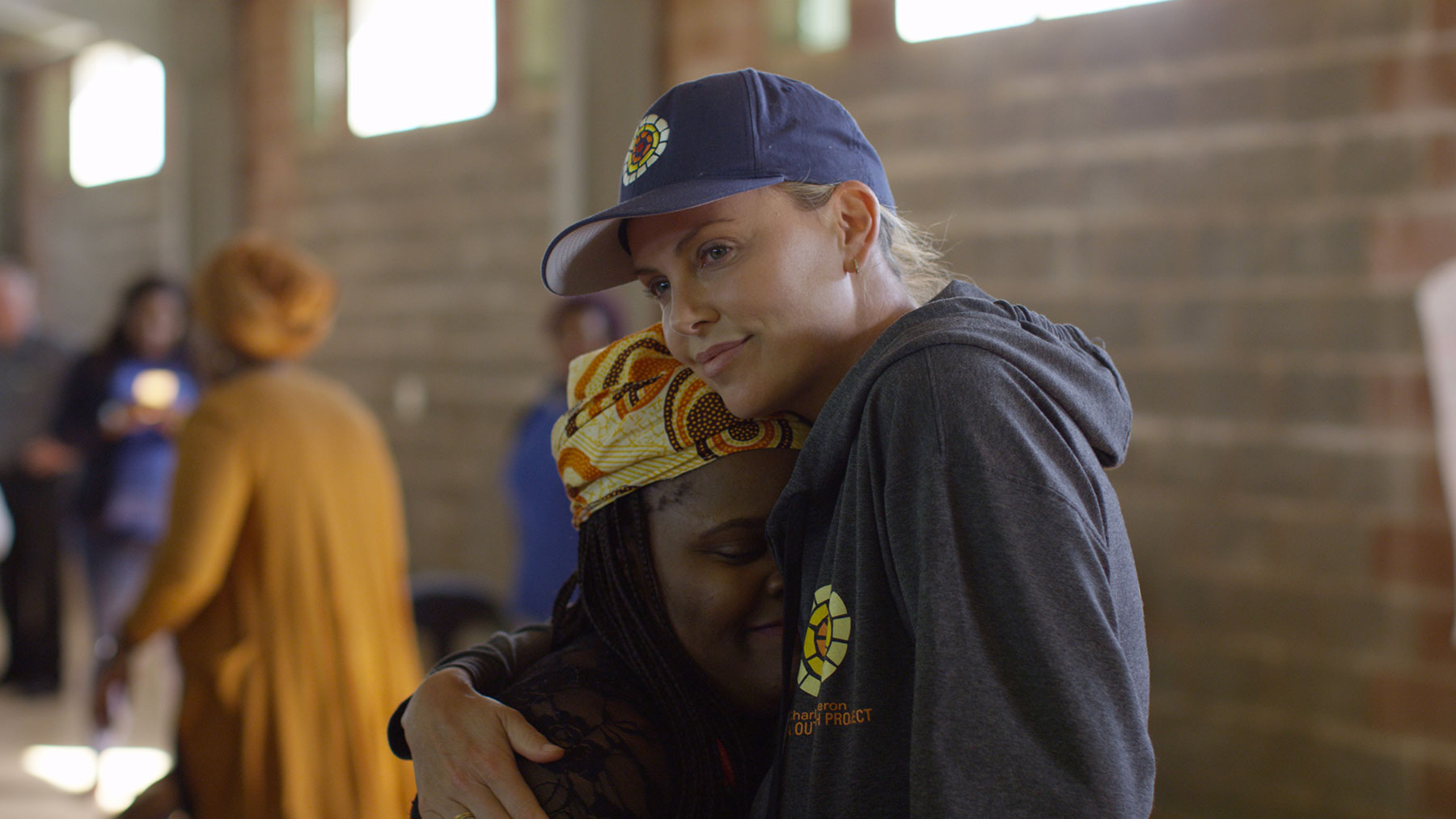 Charlize Theron hugs a young woman.