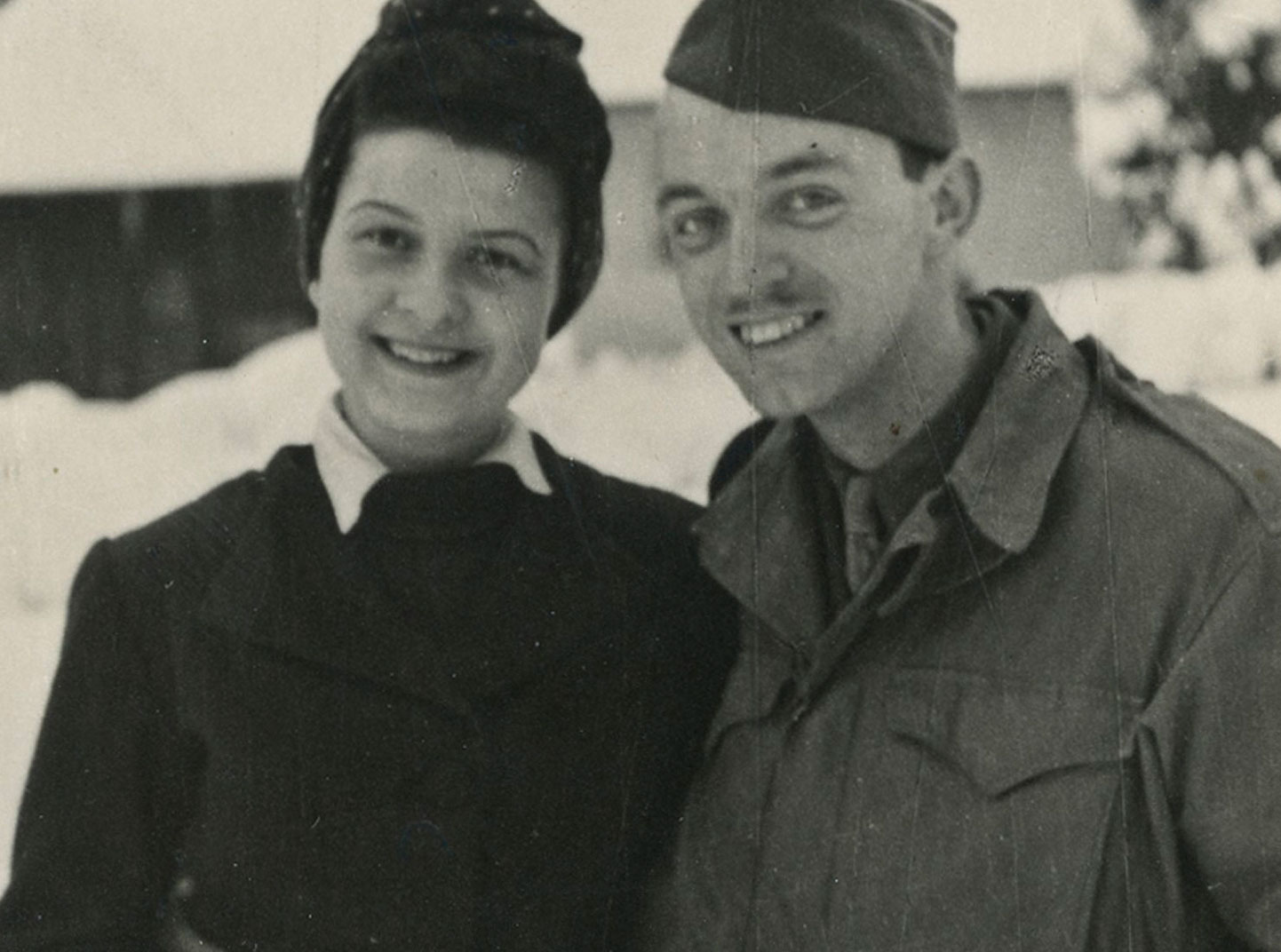 An old black and white image of a man and woman smiling and standing in the snow.
