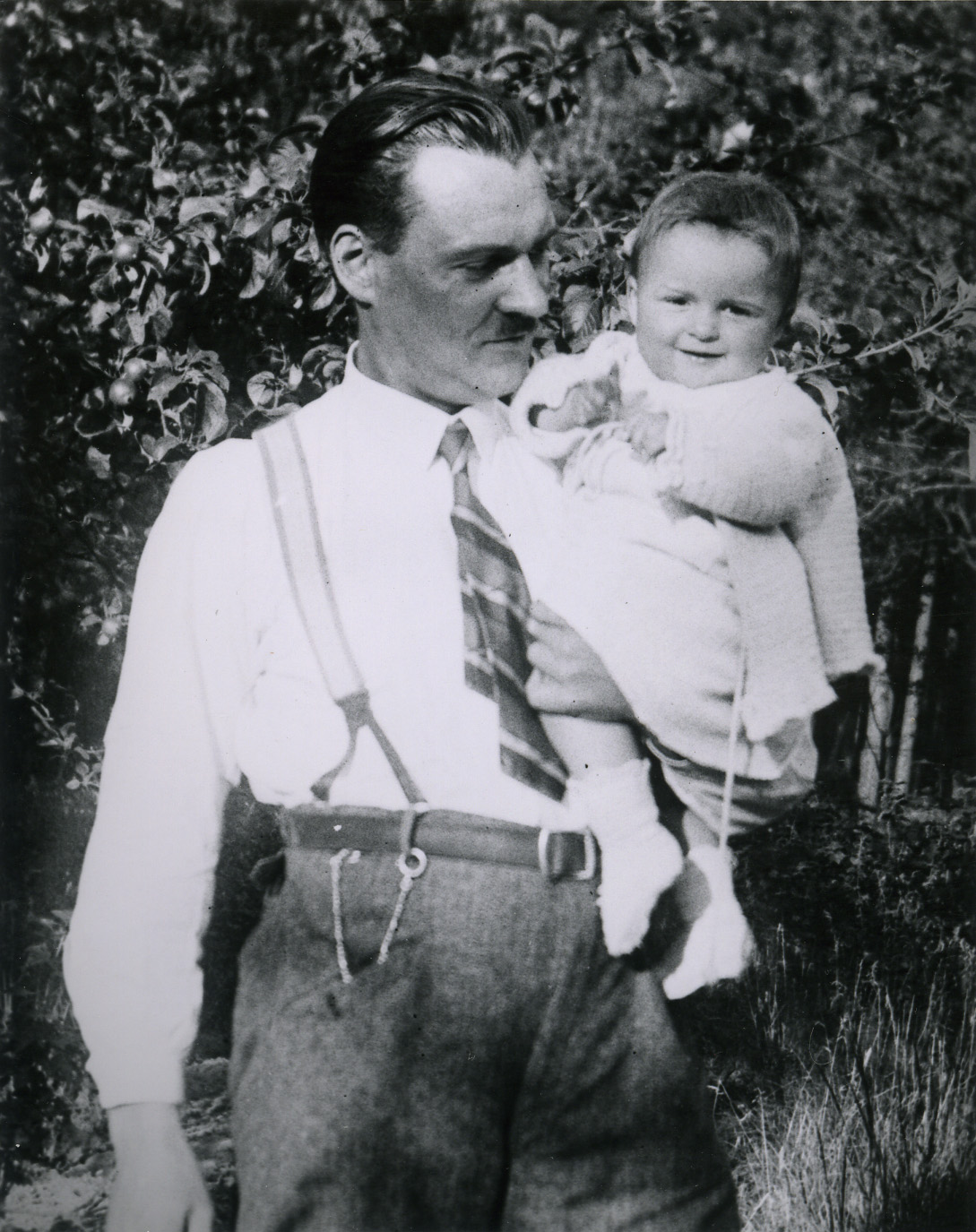 A man wearing a tie and suspenders holds a small girl.