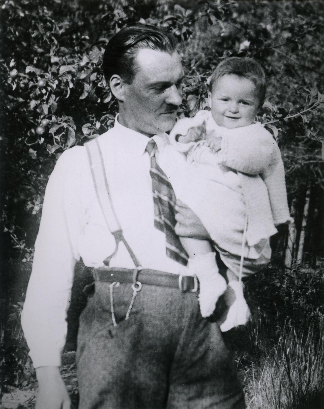 Um homem de gravata e suspensórios segura uma menina.