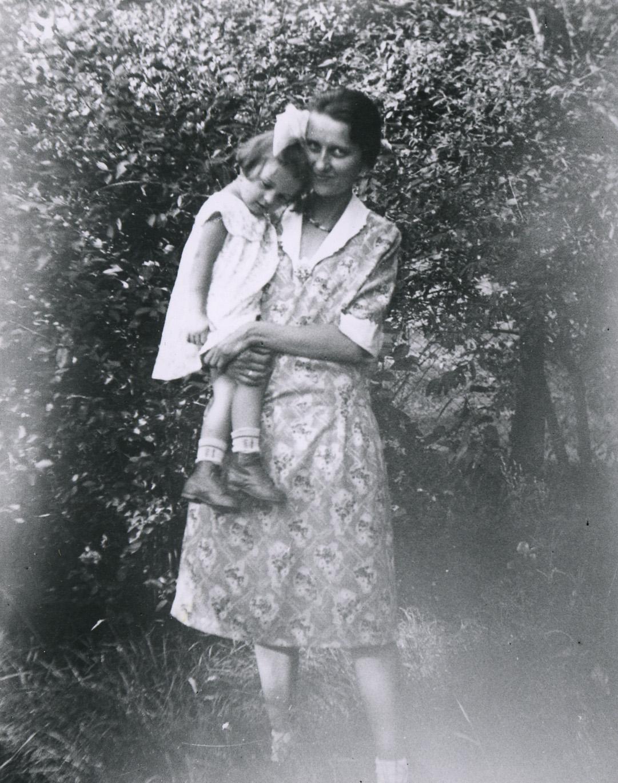 Uma mulher de vestido segura uma menina.