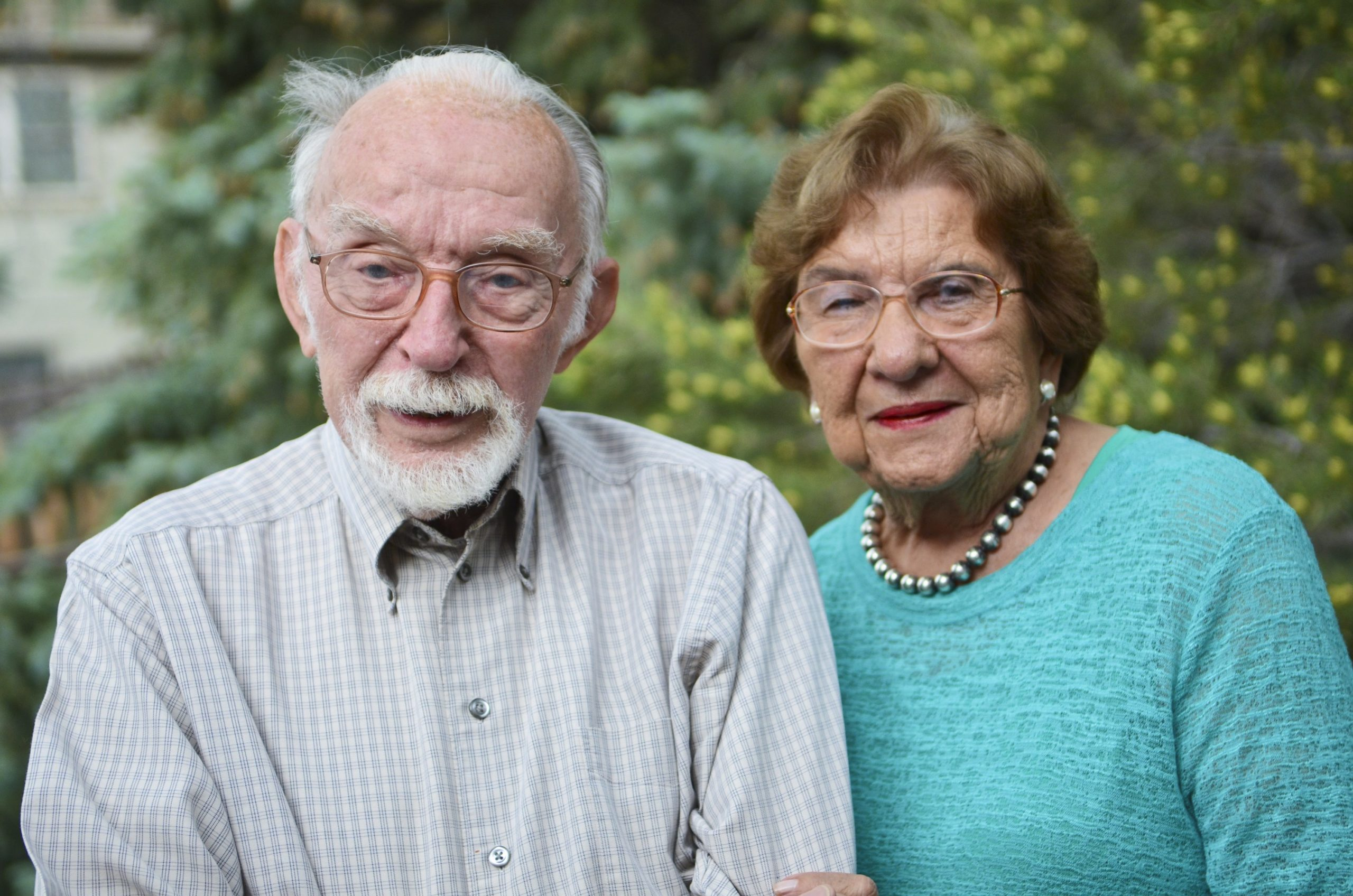 An elderly man and woman link arms and pose for the camera.