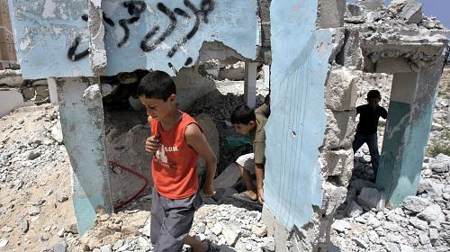 Palestinian children play over the rubble of destroyed houses. CREDIT:Khalil Khokho/CARE