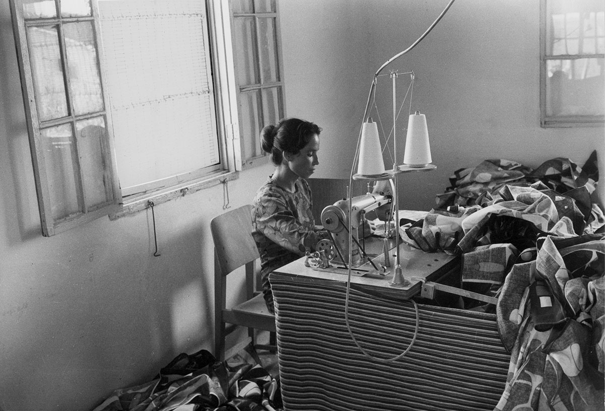 A woman sits at a desk and sews on a sewing machine.