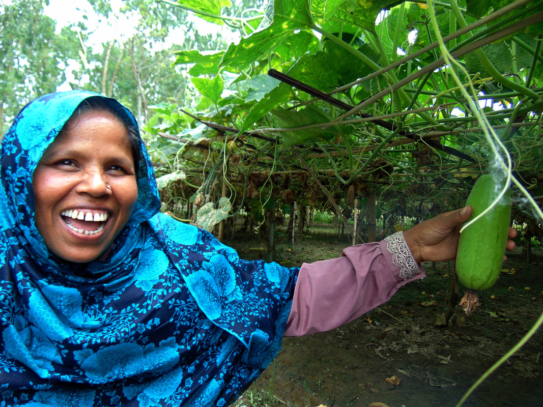 A woman wearing a bright blue headscarf flashes a big smile while showing off some of her crops.