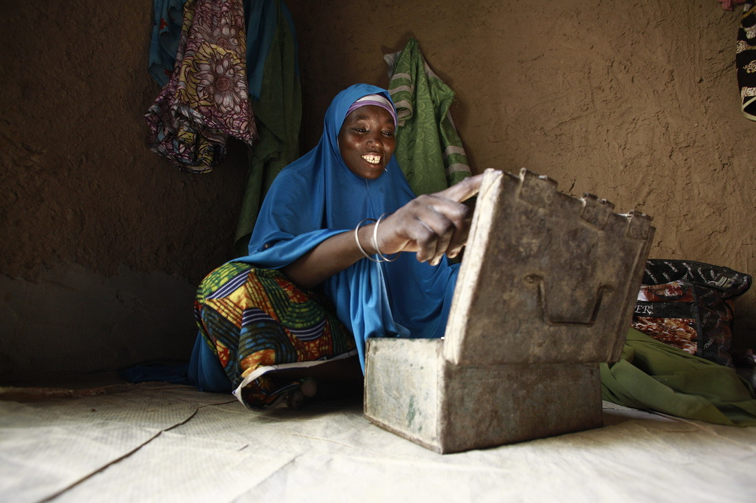 A woman wearing bright royal blue smiles as she opens a metal box on the floor.