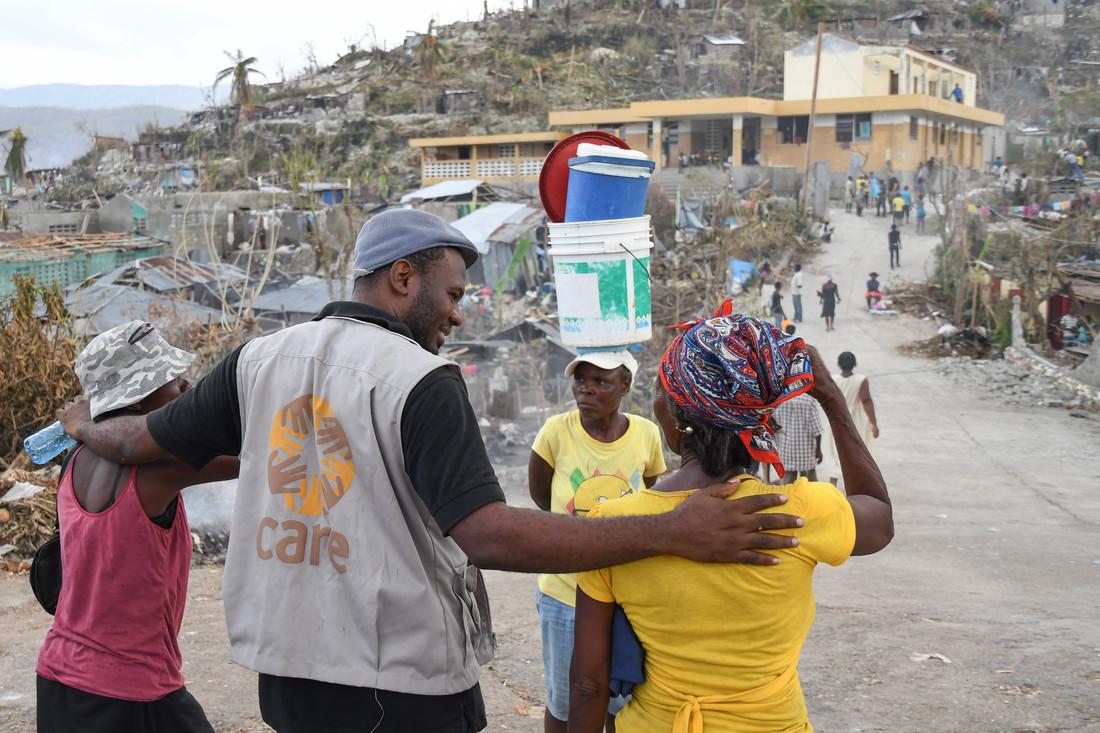 Un miembro del personal de CARE con un chaleco color canela de CARE camina con un pequeño grupo de personas por una carretera en Haití.
