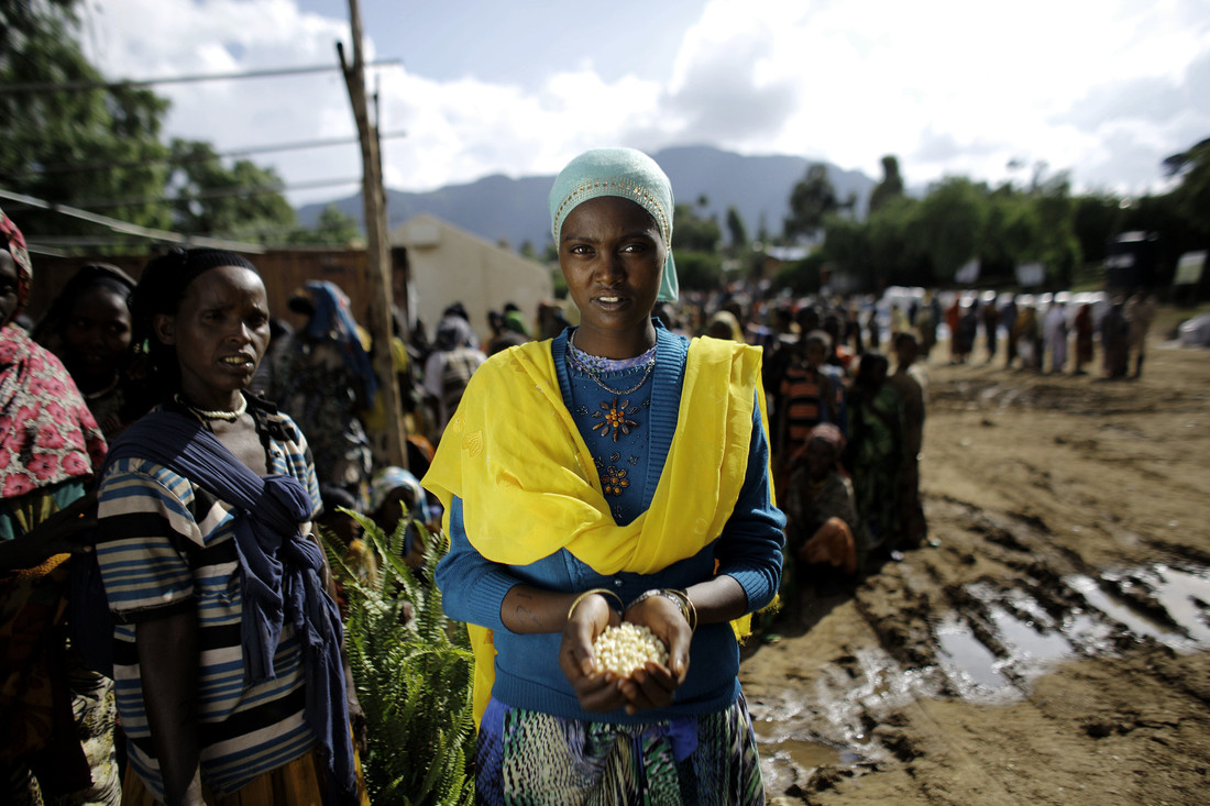 A woman wearing a bright yellow scarf cups her hands in front of her to hold a pile of seeds. Behind her you can see a large group of women.