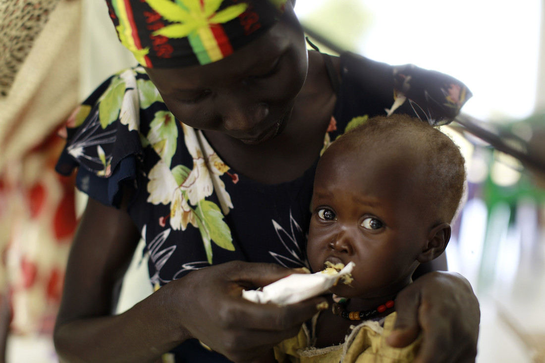A woman hand-feeds a baby food. The baby is looking at the camera.