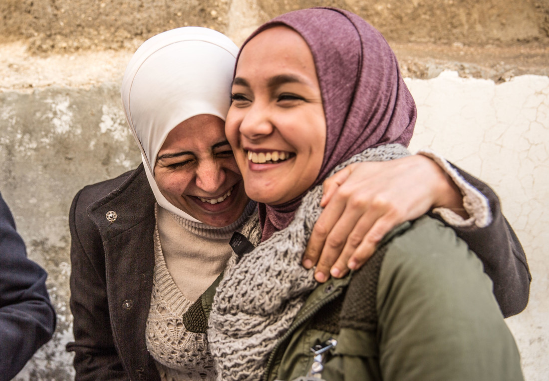 Una niña sonríe y ríe con su brazo envuelto alrededor de otra niña.