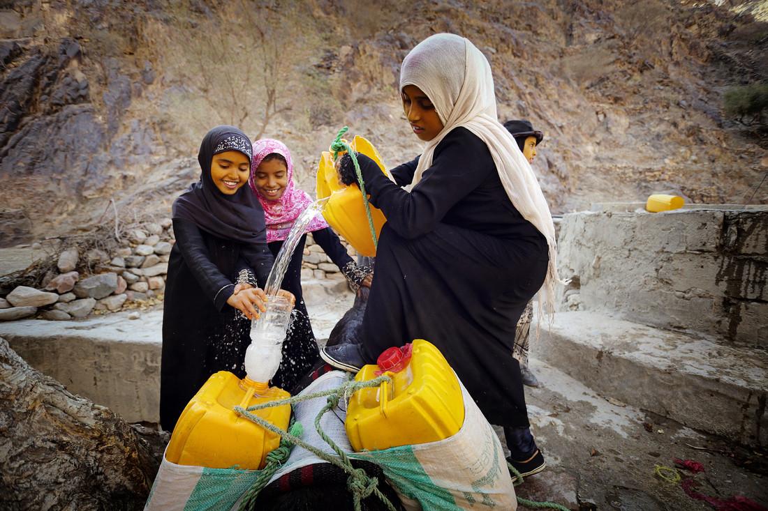 Uma garota despeja água de um balde preso a um poço em jarros de água.