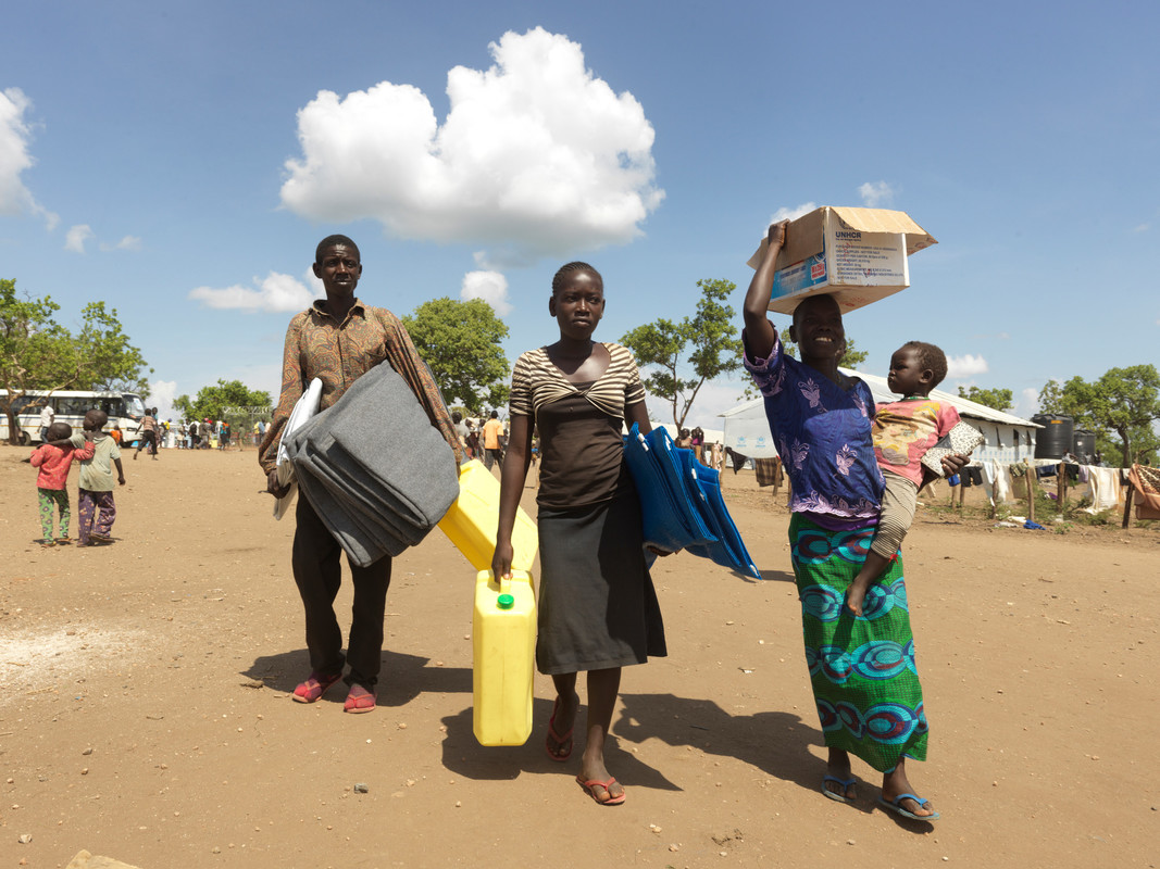 Two women and a man walk on a dirt road, all carrying blankets or buckets to hold water. The woman in front is balancing a cardboard box on her head with one arm, and carrying a baby with the other.